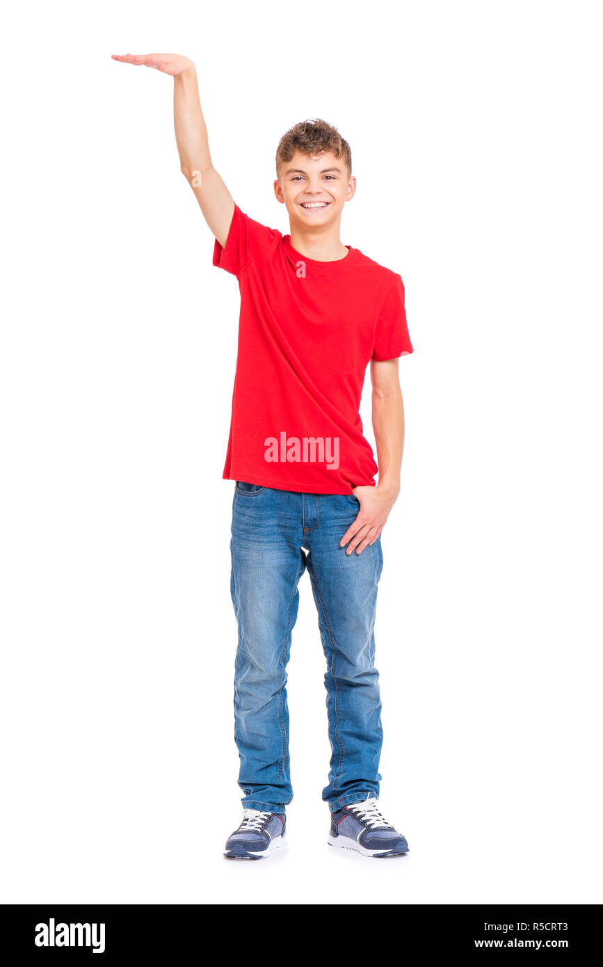 Full length portrait of young caucasian teen boy isolated on white  background. Funny teenager showing something by hand. Handsome child  looking at cam