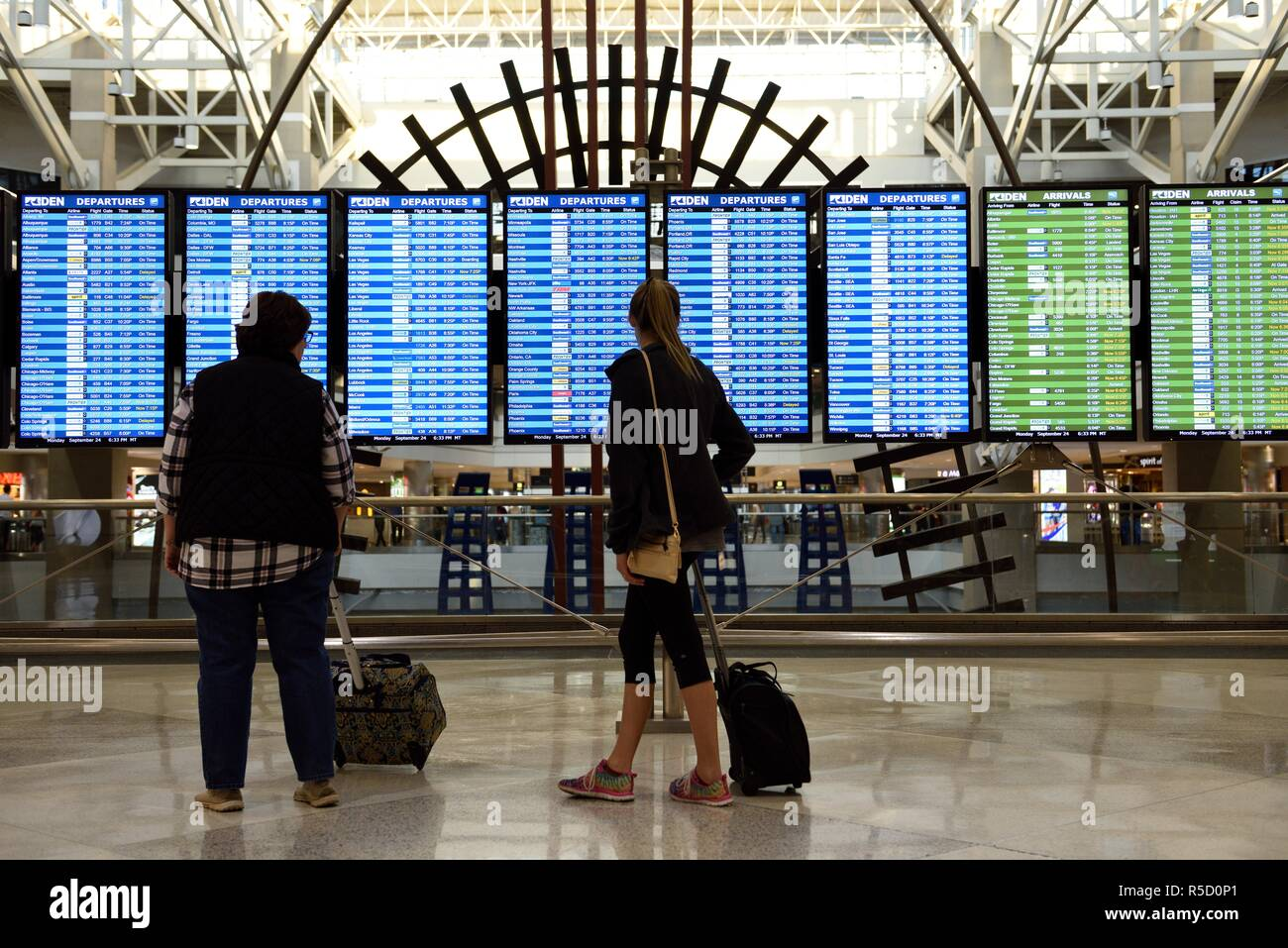 Travelers checking the flight arrival and departures information schedule display screens at Denver International Airport in Colorado, USA. - Stock Image