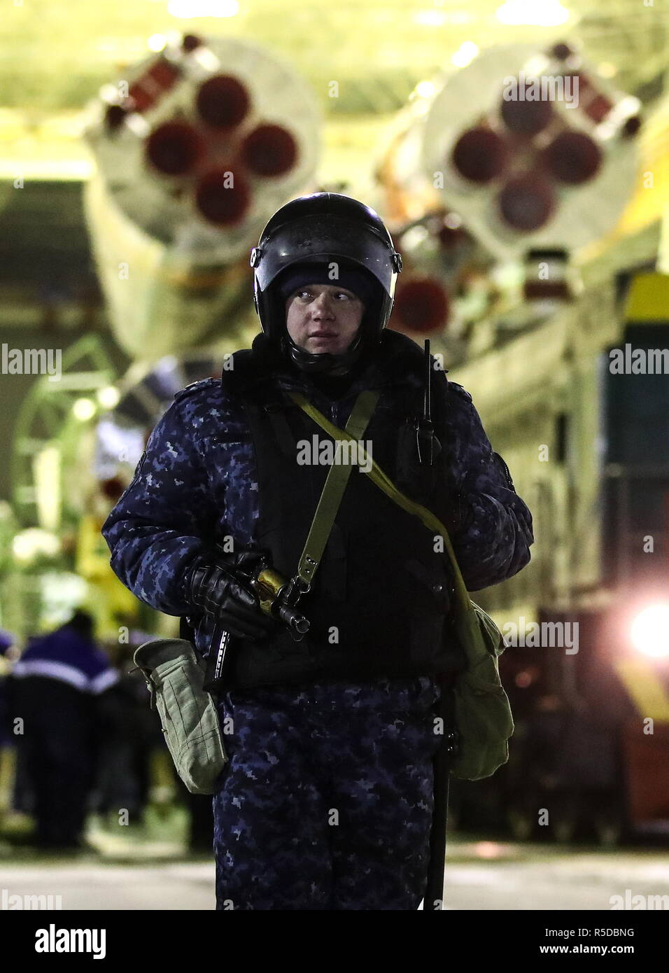 Kazakhstan. 01st Dec, 2018. KAZAKHSTAN - DECEMBER 1, 2018: An armed guard looks on as a Soyuz-FG rocket booster carrying the Soyuz MS-11 spacecraft is transported from an assembling facility to the launch pad at the Baikonur Cosmodrome. The launch of the Soyuz MS-11 spacecraft to the International Space Station (ISS) is scheduled for December 3, 2018 at 14:31 Moscow time. Valery Sharifulin/TASS Credit: ITAR-TASS News Agency/Alamy Live News - Stock Image