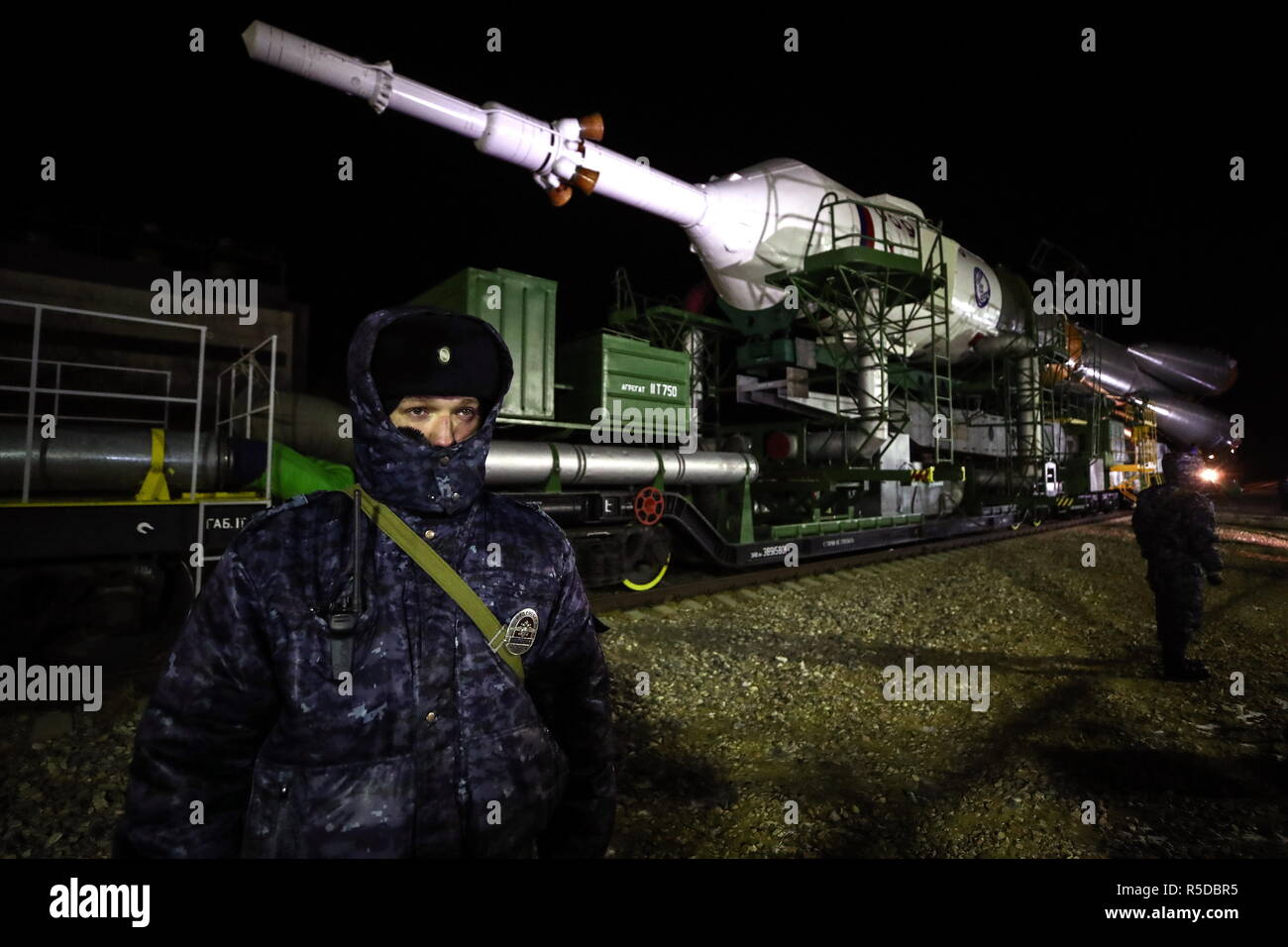 Kazakhstan. 01st Dec, 2018. KAZAKHSTAN - DECEMBER 1, 2018: Armed police stand guard as a Soyuz-FG rocket booster carrying the Soyuz MS-11 spacecraft is transported from an assembling facility to the launch pad at the Baikonur Cosmodrome. The launch of the Soyuz MS-11 spacecraft to the International Space Station (ISS) is scheduled for December 3, 2018 at 14:31 Moscow time. Valery Sharifulin/TASS Credit: ITAR-TASS News Agency/Alamy Live News - Stock Image