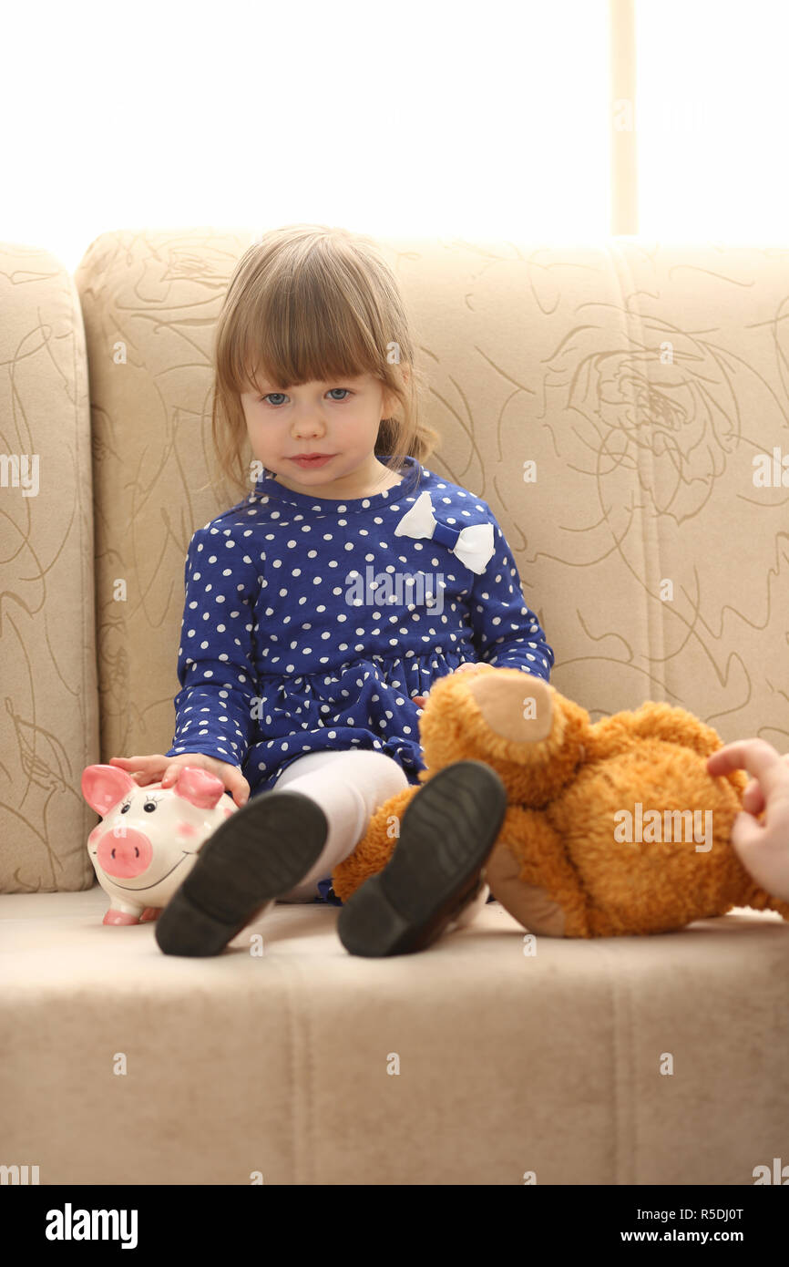 Cute little girl portrait at couch with piggybank - Stock Image