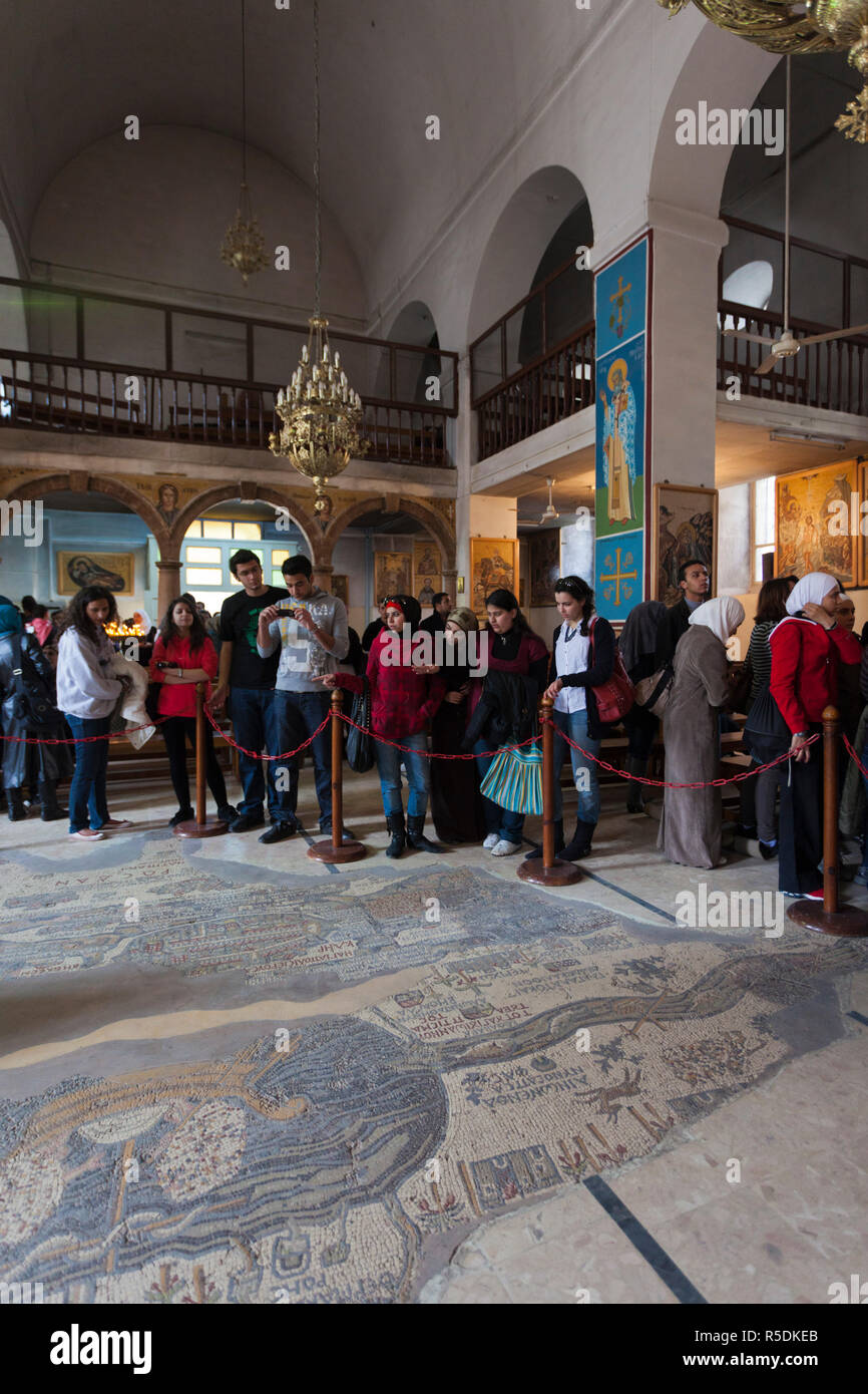 Jordan, Kings Highway, Madaba, St. Georges Church, interior with ancient Mosaic Map of the World, circa 560 AD with visitors - Stock Image