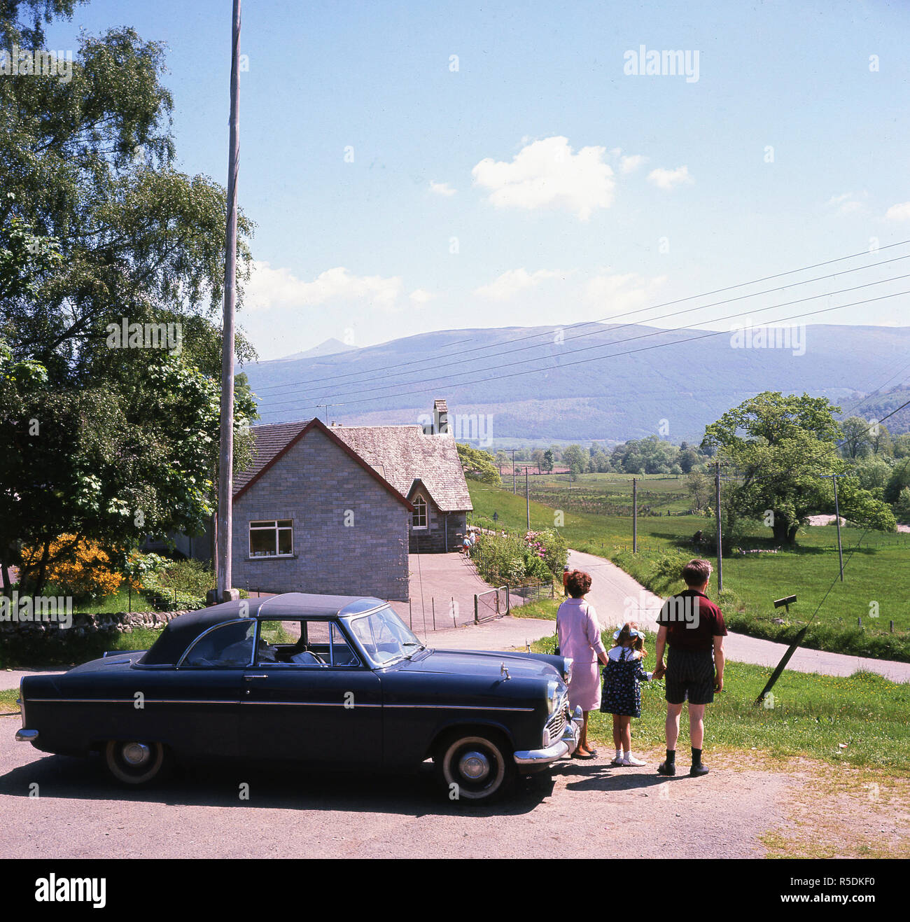 1960s, Balquhidder, Stirling, Scotland, a couple and their small child stand by their car looking at the mountain terrain of the Braes of Balquhidder that overlooks the village. The famous Scottish outlaw and folk hero, Rob Roy lived and died in Balquhidder. Stock Photo