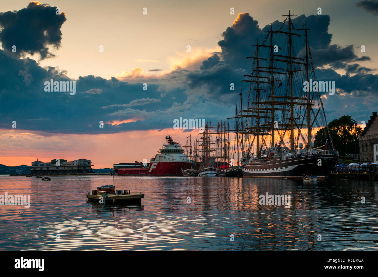 Bergen Harbour at sunset with mix of ships on the water. Tall ship races Bergen, Norway 2014 - Stock Image