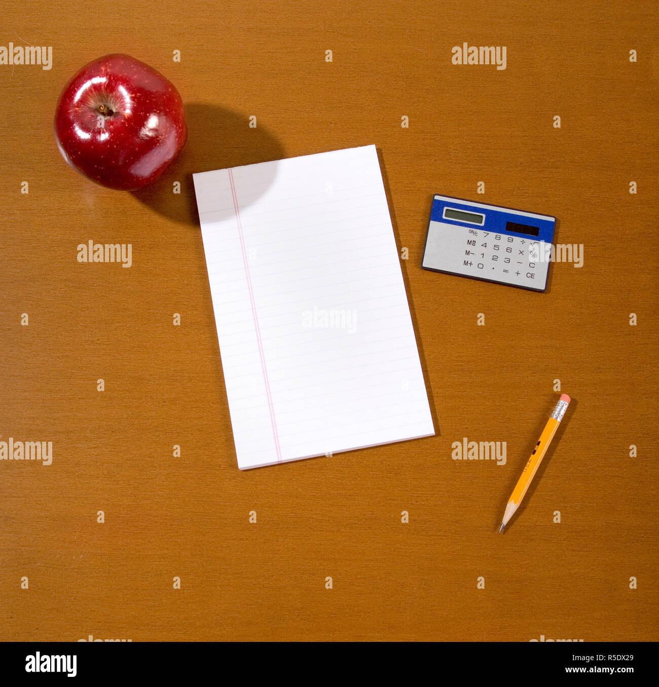 Teachers desk with short pencil, calculator, red apple, pad