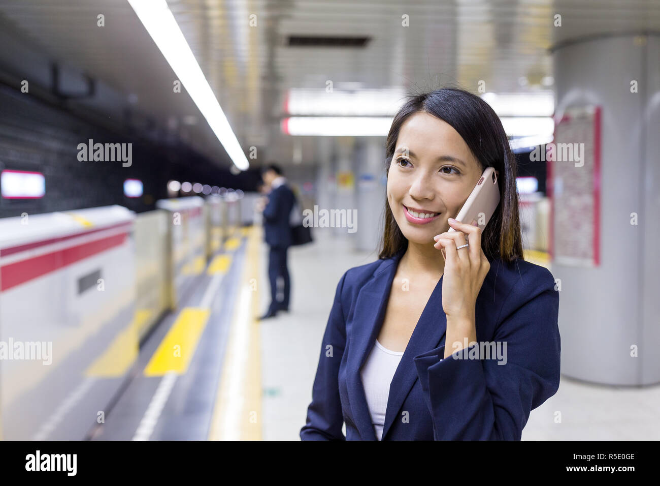 Young Businesswoman talk to cellphone in train station Stock Photo