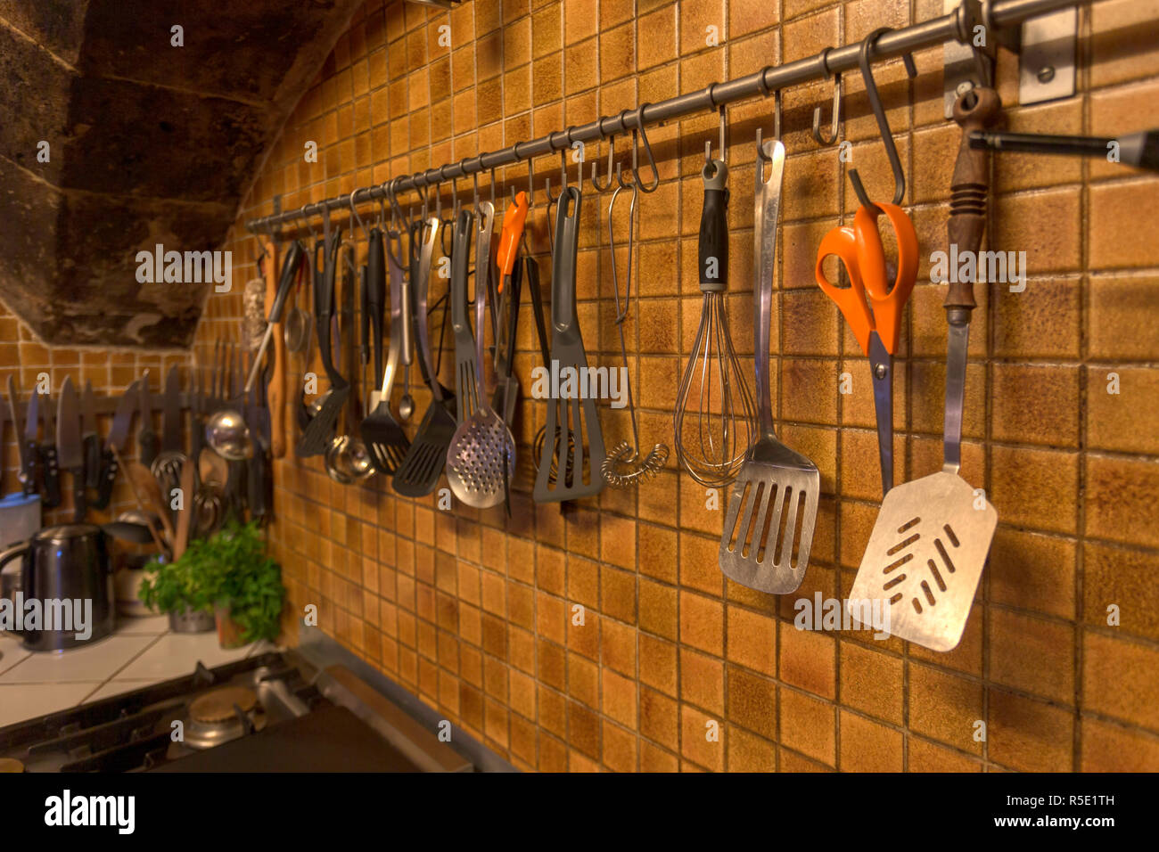 Kitchen utensils hanging on the wall of a vintage kitchen. Stock Photo