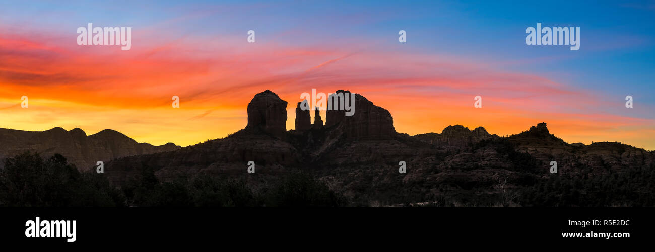 A colorful sunrise sky silhouettes Cathedral Rock and the surrounding rugged landscape of Sedona, Arizona. Stock Photo