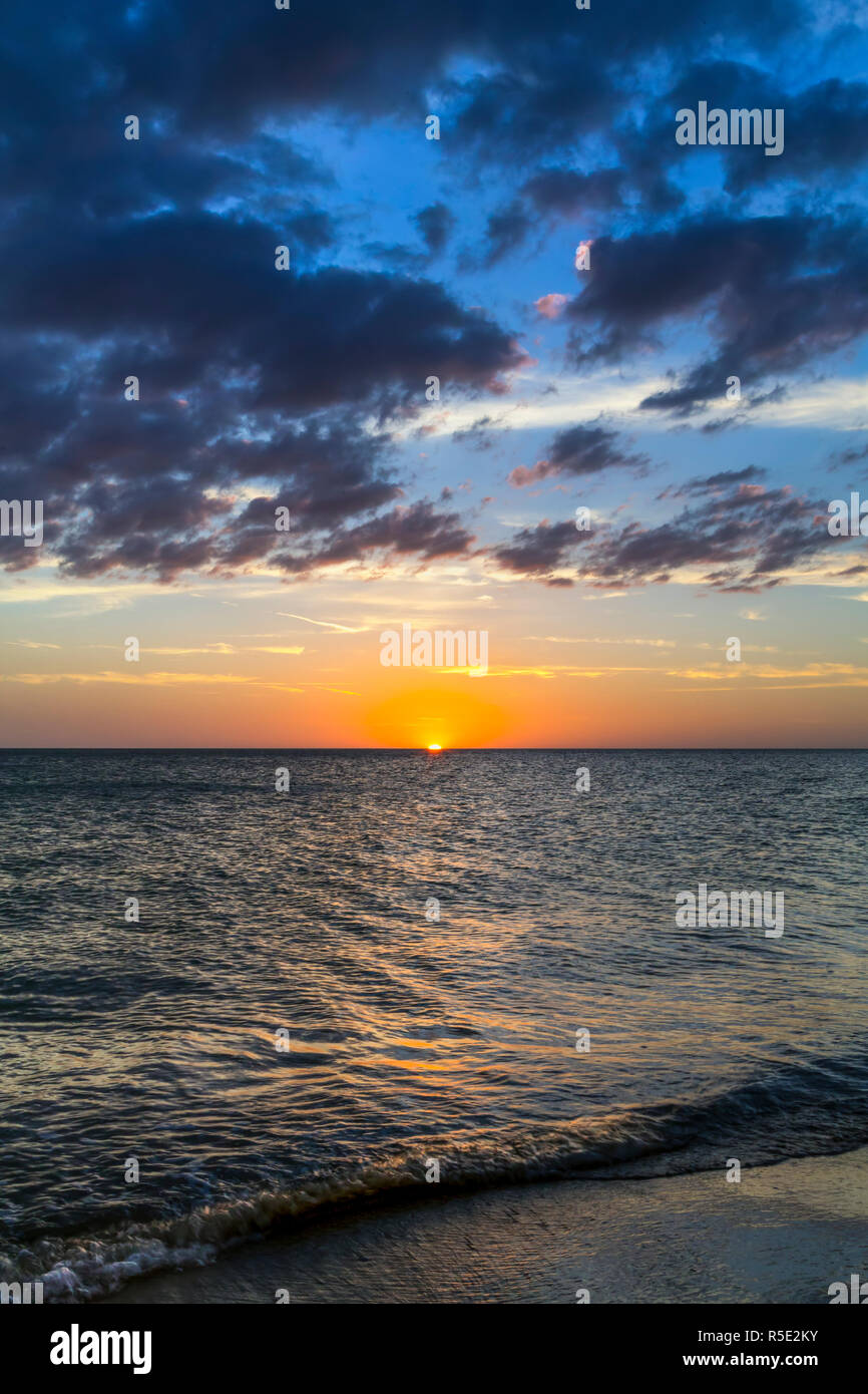 A beautiful sunset over the Gulf of Mexico is viewed from the beach at Treasure Island, Florida. Stock Photo