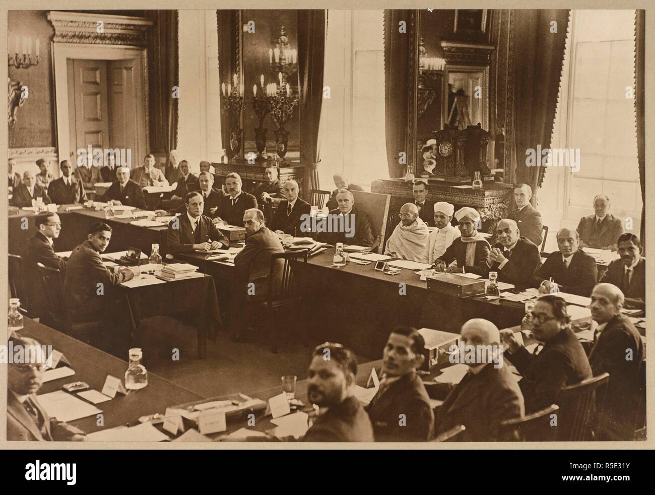 Delegates at the second session of the Indian Round Table Conference, St. James's Palace, London. A group portrait of delegates seated at the Chairman's table, British delegates to the left, Indian to the right. From left to right: Lord Pethick-Lawrence; Lord Lothian; Lord Peel; Sir Samuel Hoare; Lord Sankey; Mahatma Gandhi; Madan Mohan Malaviya; --; Sir Tej Bahadur Sapru. The Round Table Conference (Second Session), St James' Palace, London. Sep. 1931. Photograph. Source: Photo 13/(1). Author: UNKNOWN. Stock Photo