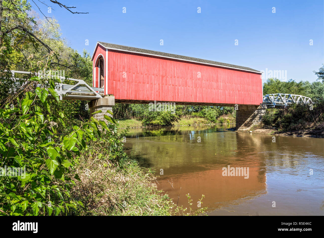The red Wolf  Covered Bridge, with pony truss approaches, crosses the Spoon River in rural Knox County, Illinois. Stock Photo