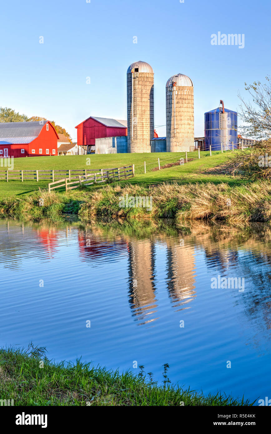 Early morning sunrise glow illuminates a farm with red barns and silos reflected in the waters of Illinois' Apple River. Stock Photo