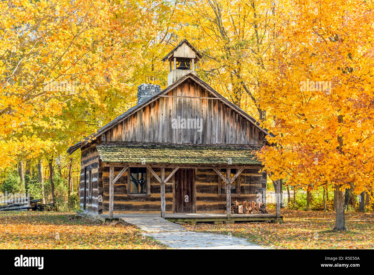 A log church is surrounded by colorful autumn trees in an Indiana park. Stock Photo