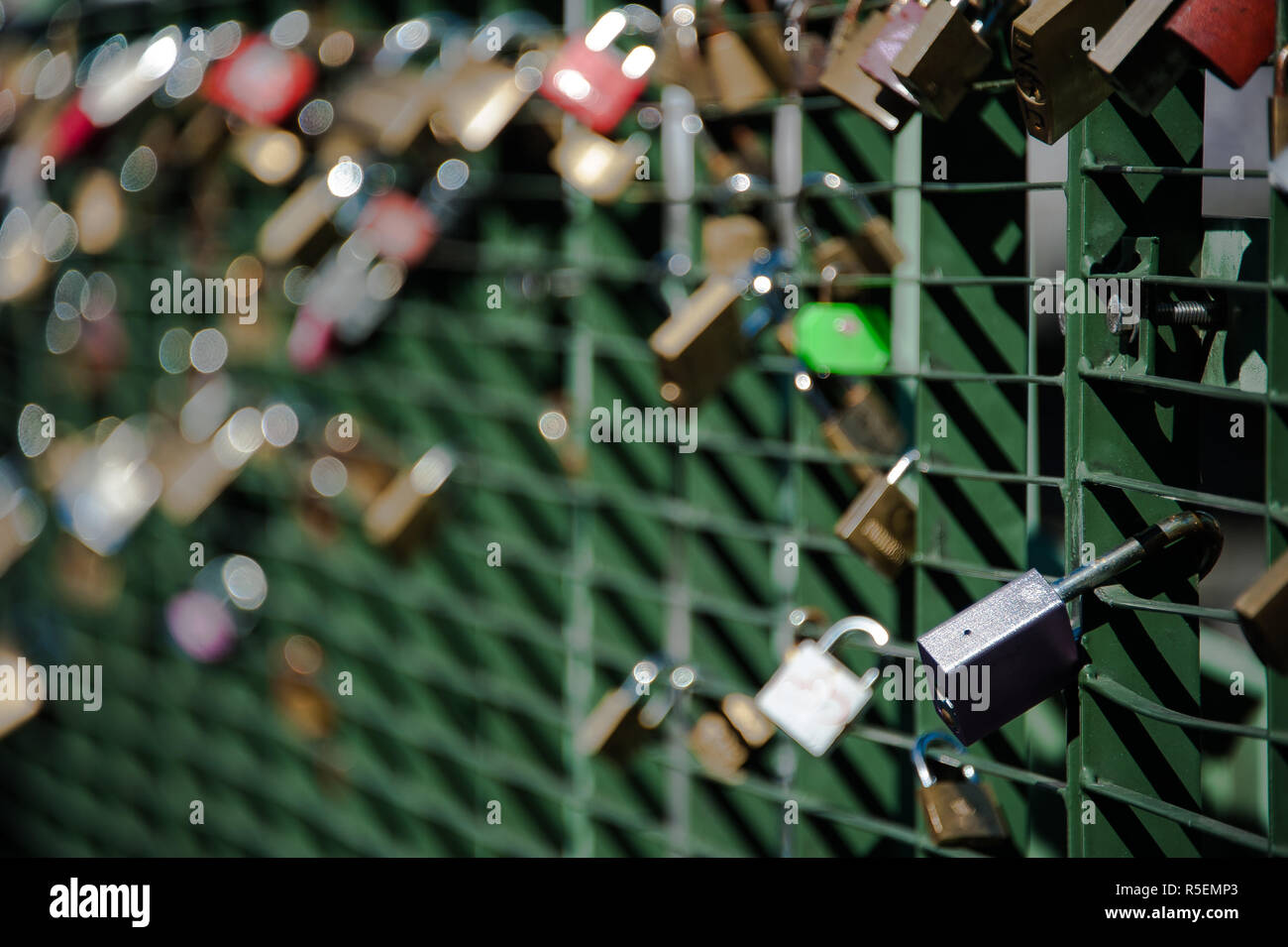 Padlocks attached to metal bridge railing across river l'Arve - Stock Image
