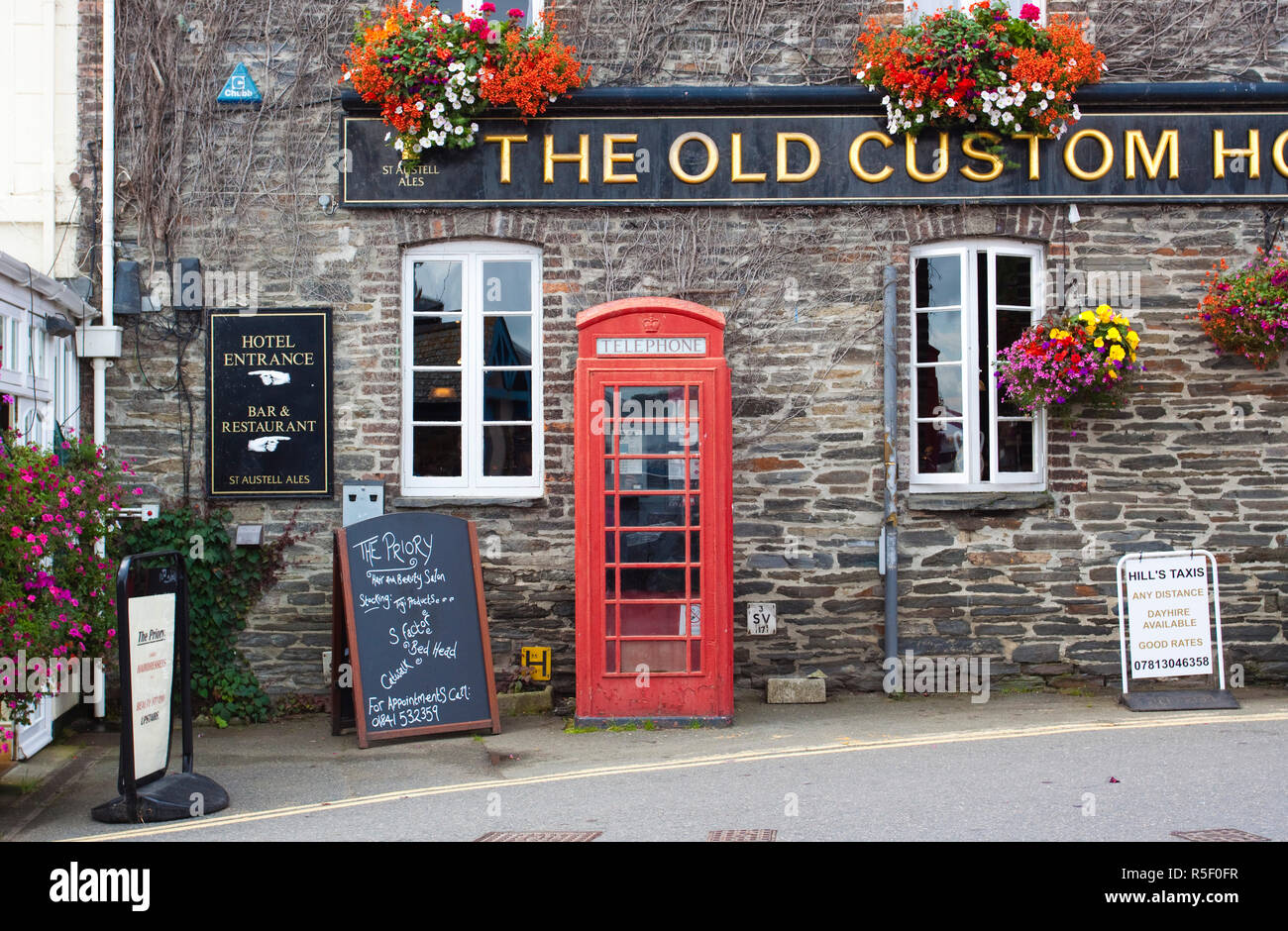 Telephone box outside pub, Padstow, Cornwall, England - Stock Image