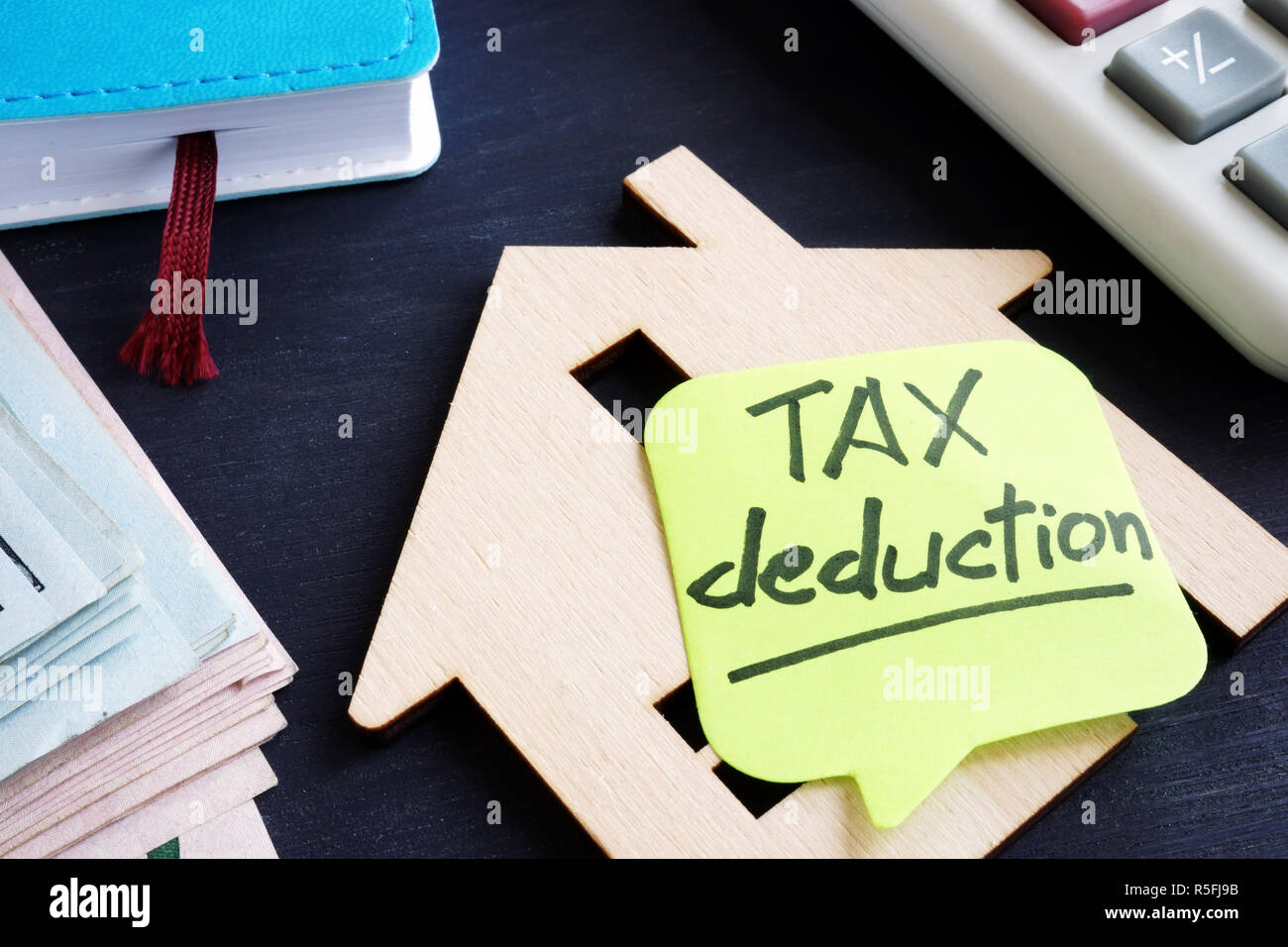 Property tax deduction. Model of house and calculator. - Stock Image