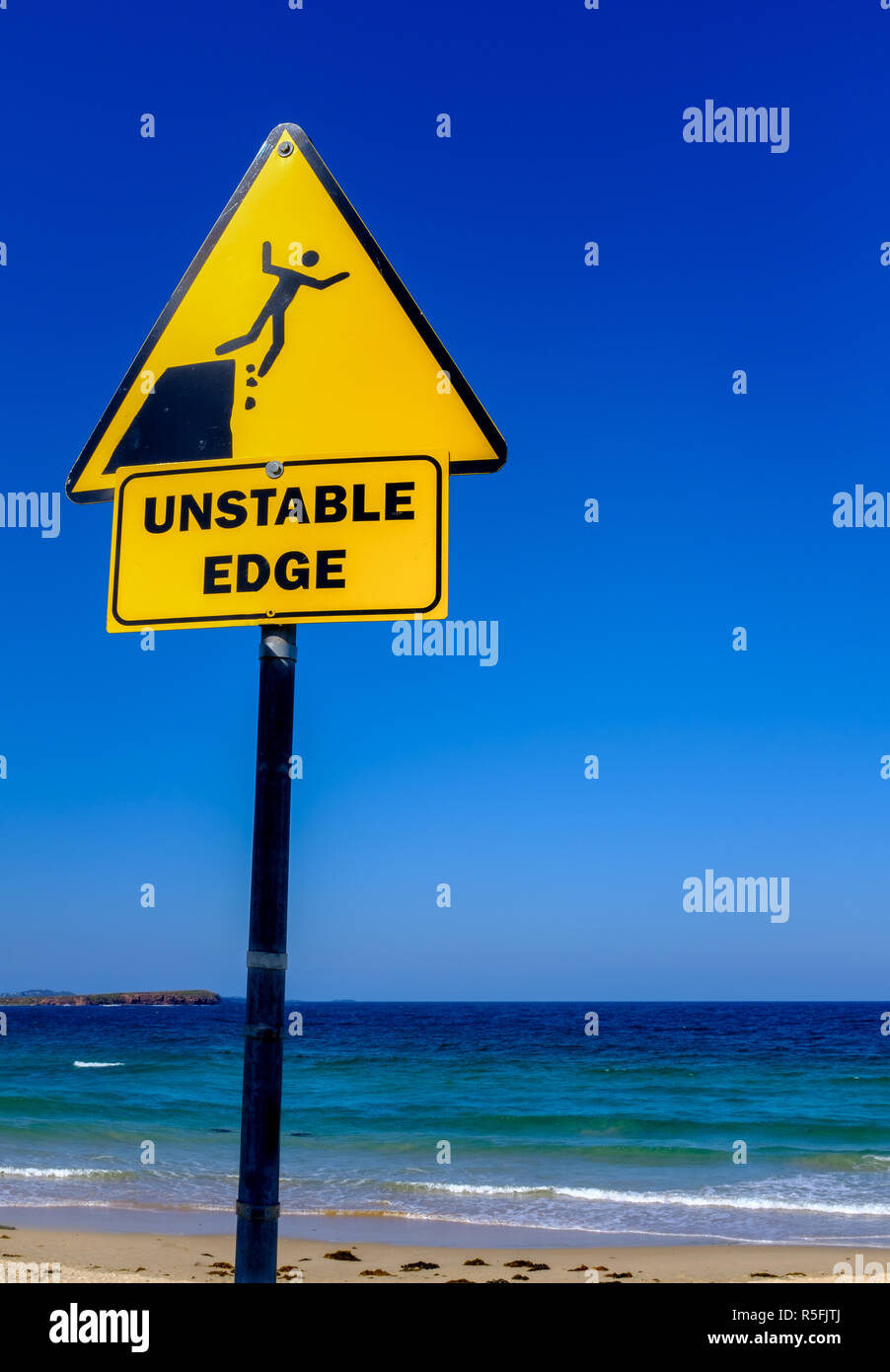 Unstable edge sign overlooking sea, person falling off cliff, Australian signs - Stock Image