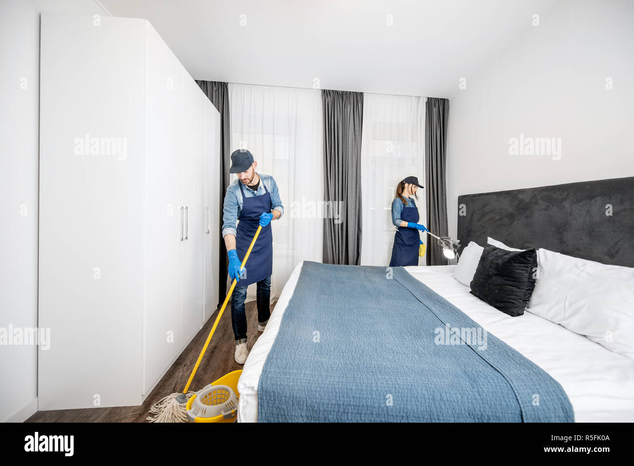 Professional Cleaners In Uniform Washing Floor And Wiping Dust From The Furniture In The Hotel Room Or Apartment Bedroom Cleaning Service Concept Stock Photo Alamy