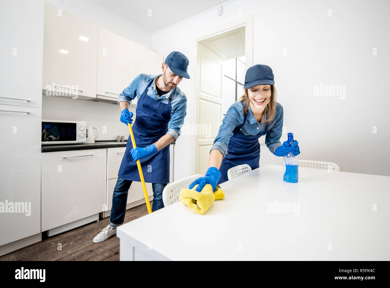 Man and woman as a professional cleaners in uniform washing ...