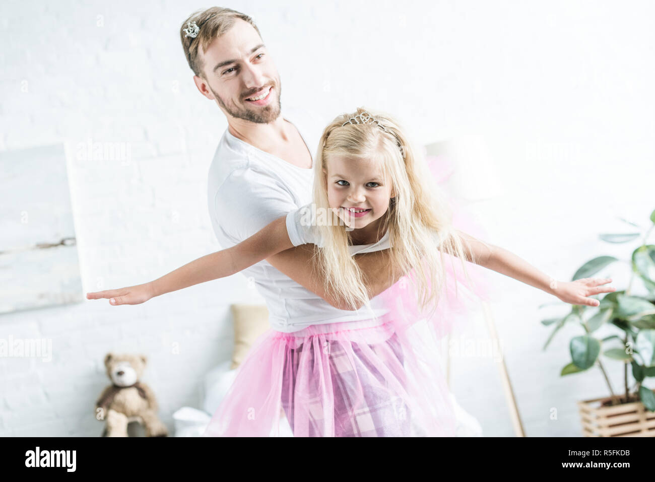 happy father and daughter in pink tutu skirts dancing at home - Stock Image