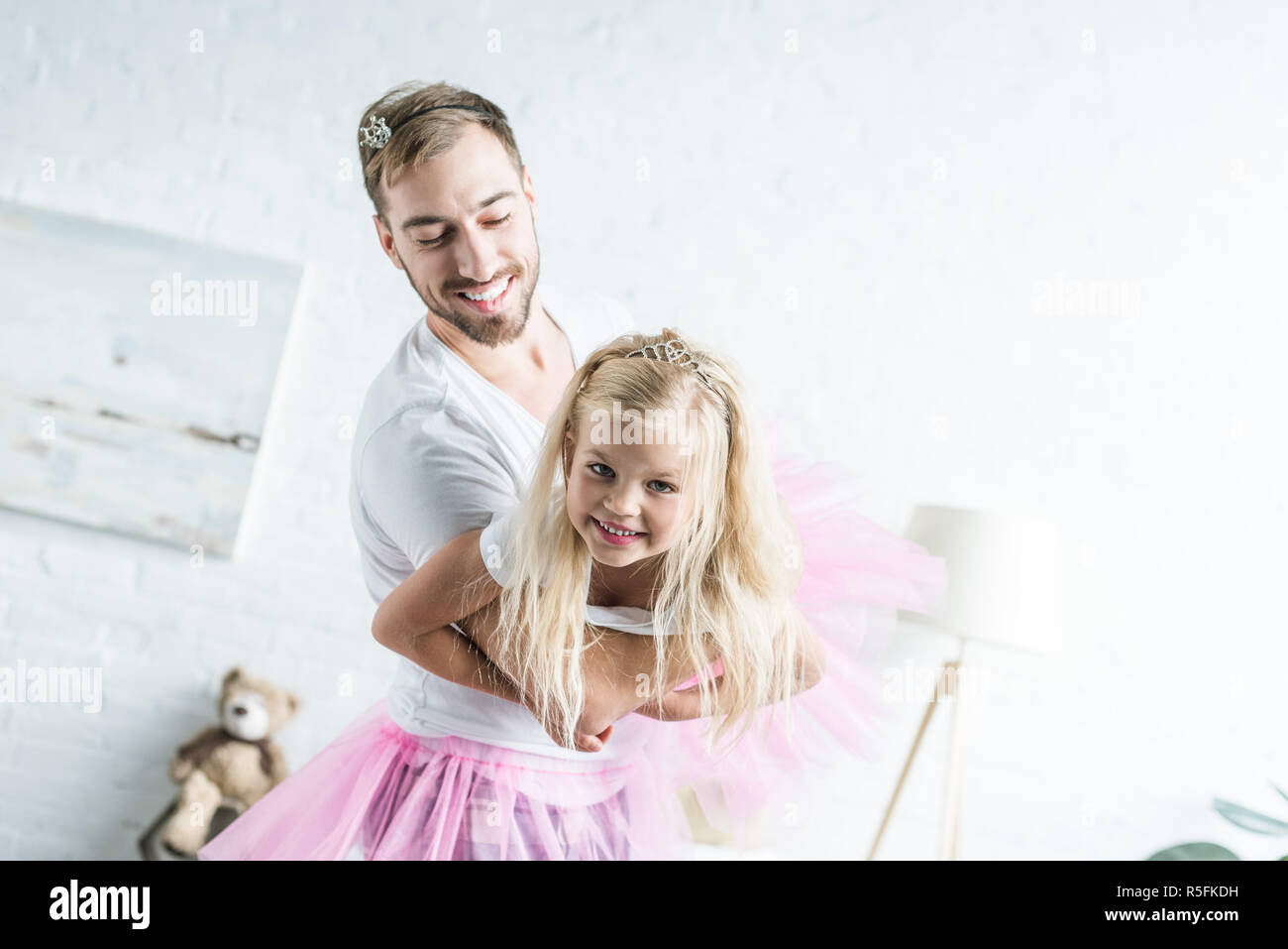 happy father and adorable little daughter in pink tutu skirts dancing at home - Stock Image