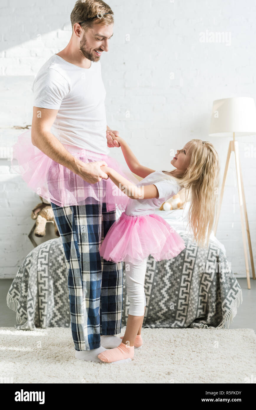side view of happy father and little daughter in pink tutu skirts holding hands and dancing at home - Stock Image