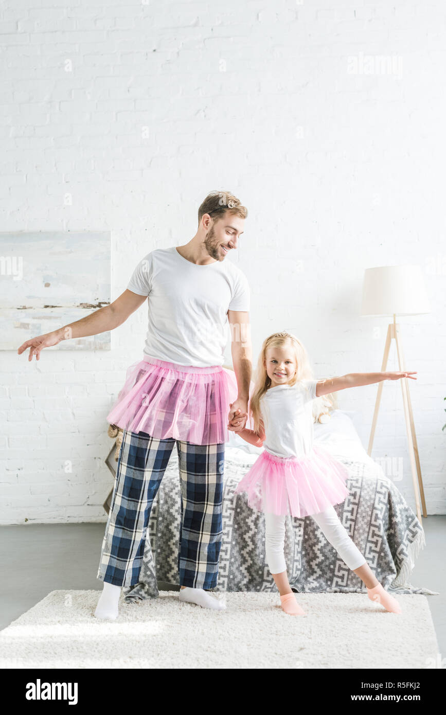 happy father and cute little daughter in pink tutu skirts holding hands and dancing at home - Stock Image
