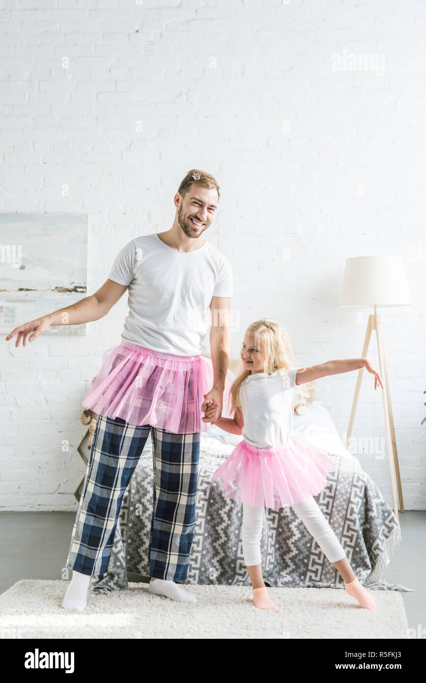 happy father and adorable little daughter in pink tutu skirts holding hands and dancing at home - Stock Image