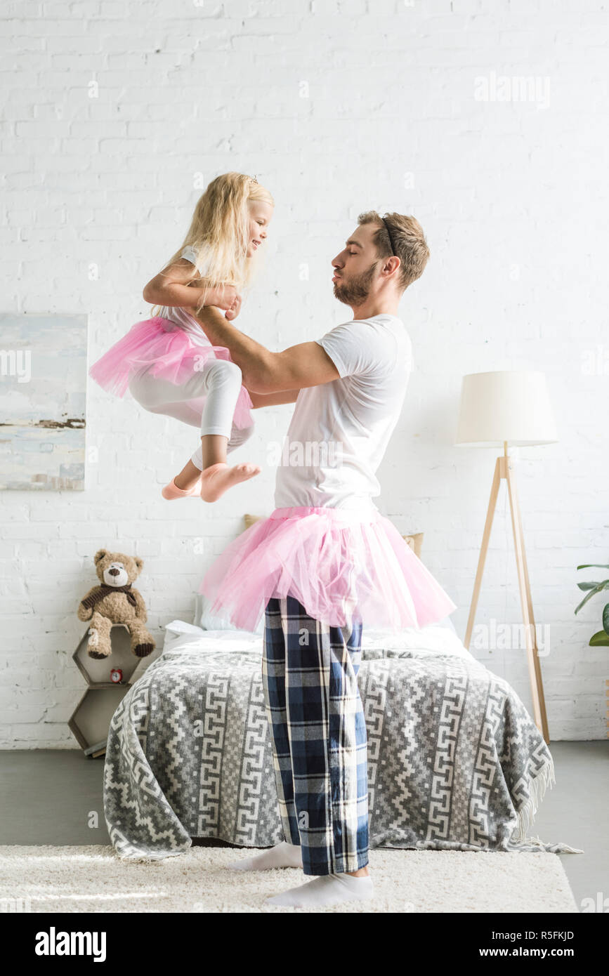 side view of happy father and cute little daughter in pink tutu skirts dancing at home - Stock Image