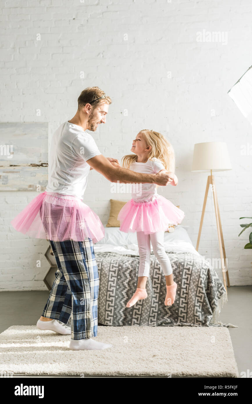 happy father and cute little daughter in pink tutu skirts dancing at home - Stock Image