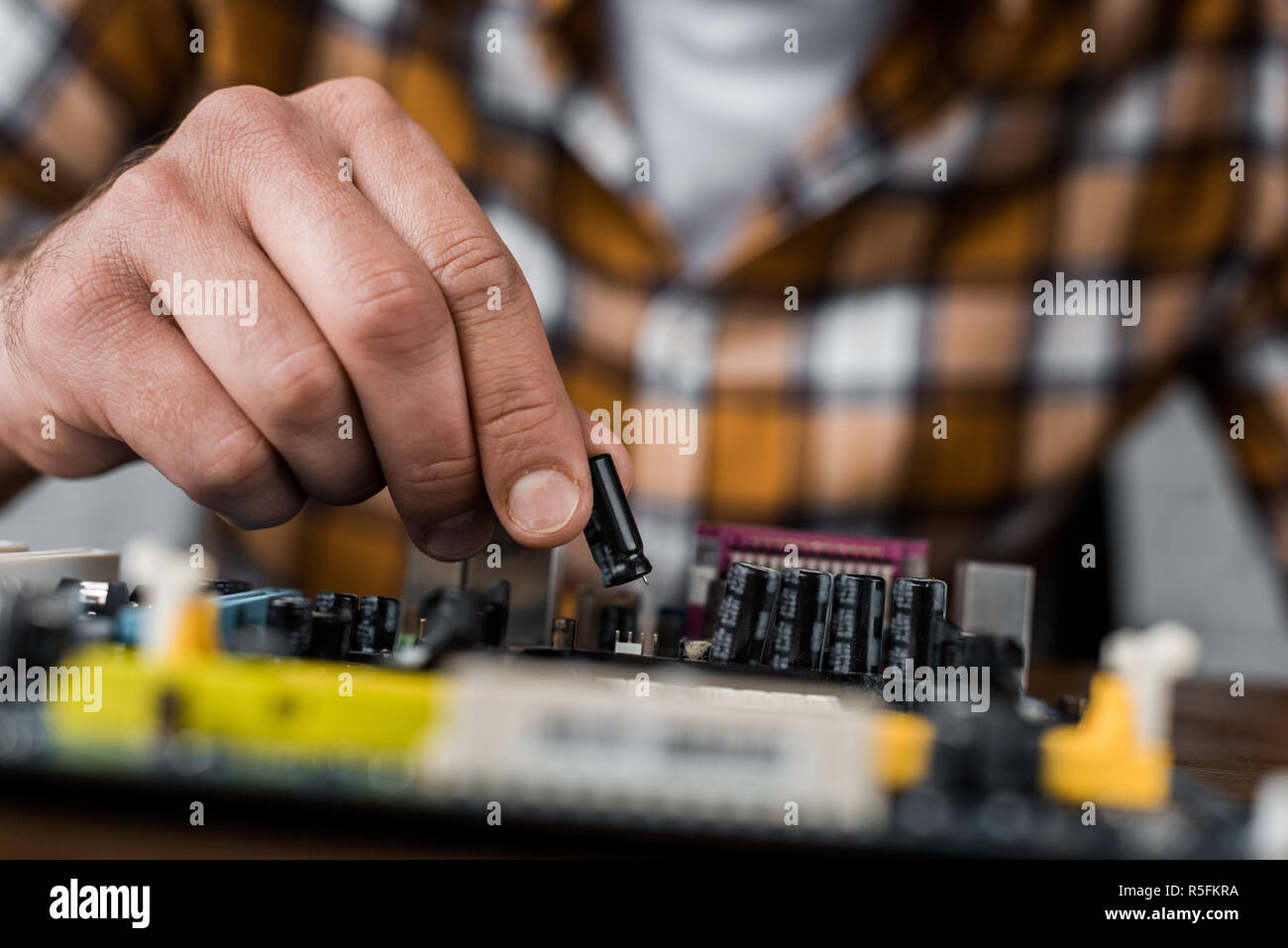 cropped shot of computer engineer taking transistor from motherboard - Stock Image