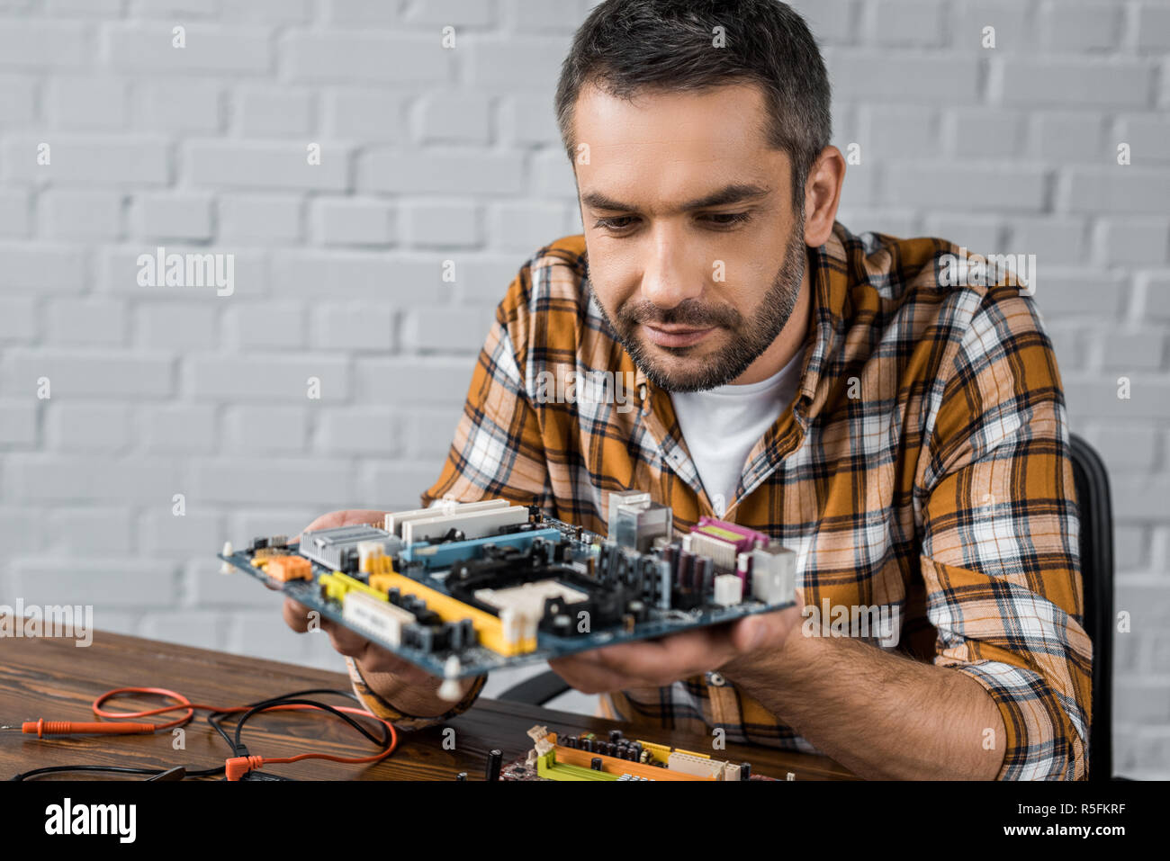 serious handsome computer engineer holding motherboard - Stock Image