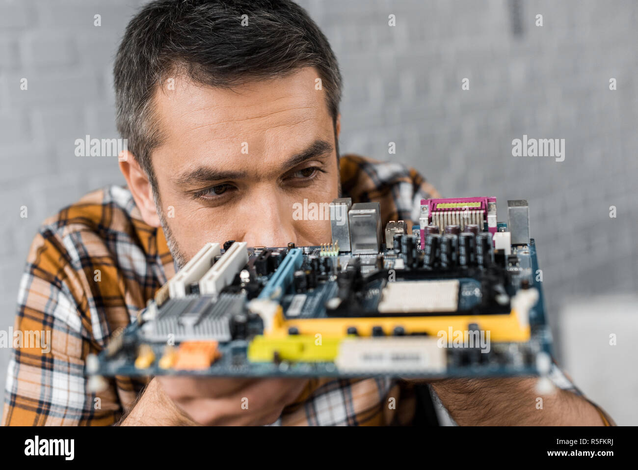close-up portrait of handsome computer engineer with motherboard - Stock Image