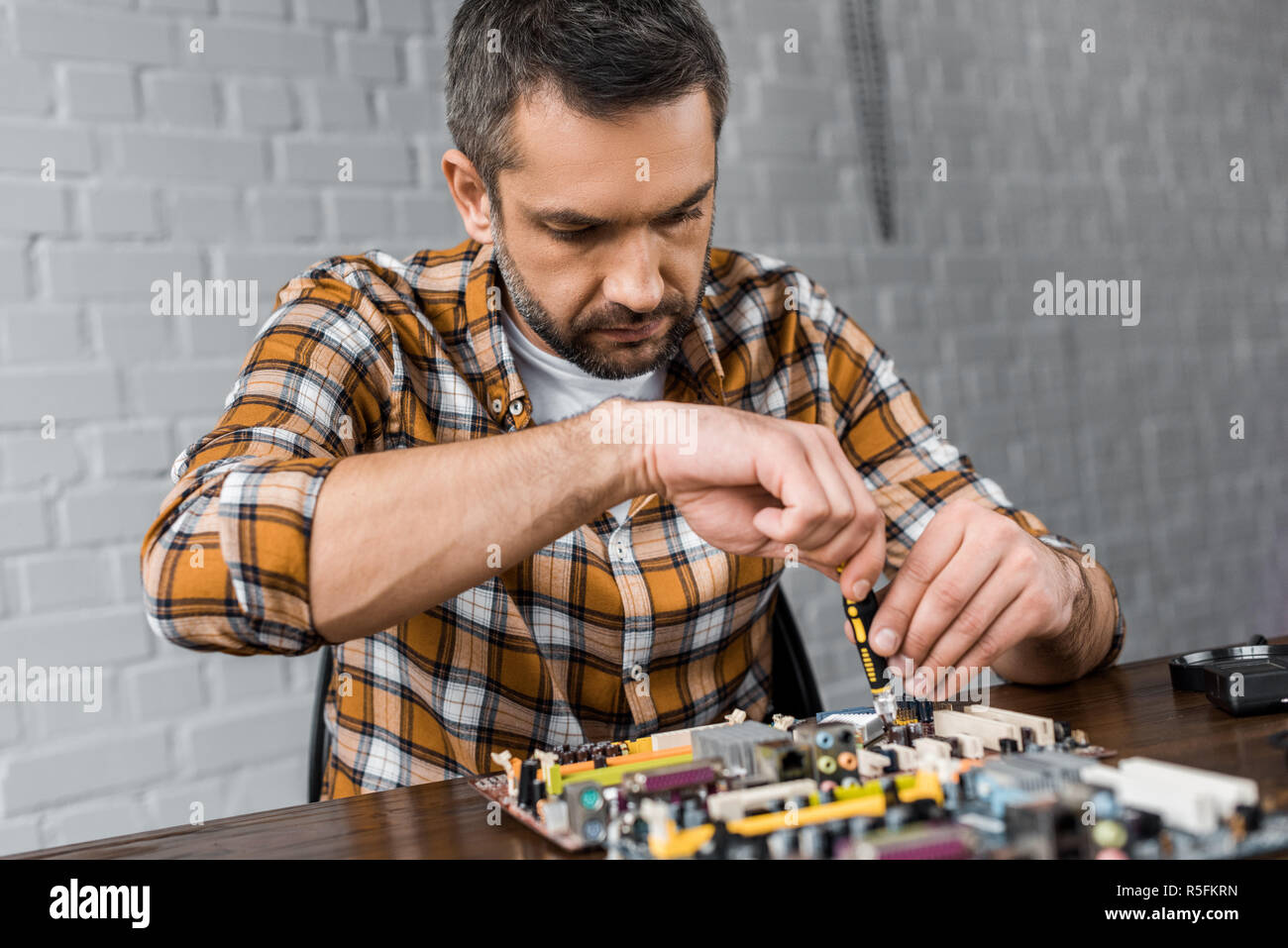 computer engineer repairing motherboard with screwdriver - Stock Image