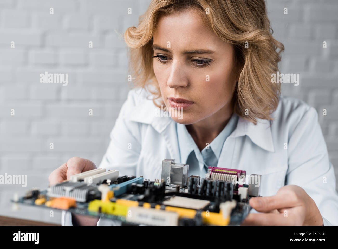 close-up portrait of female computer engineer holding motherboard - Stock Image