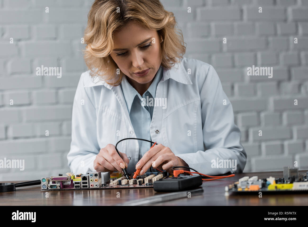 female computer engineer with tester examining motherboard - Stock Image