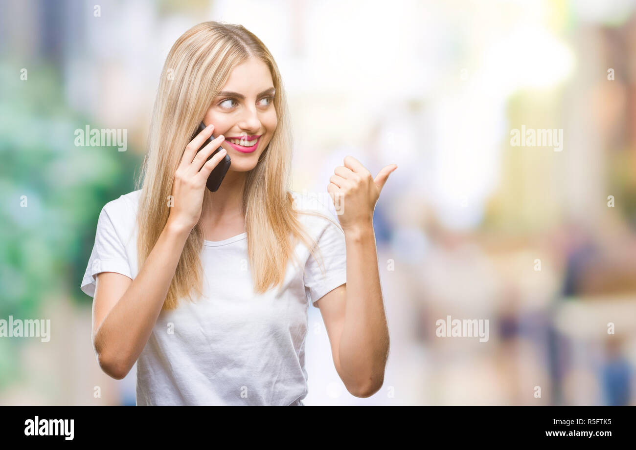 f9ad870ddc723 Young beautiful blonde woman talking using smartphone over isolated  background pointing and showing with thumb up