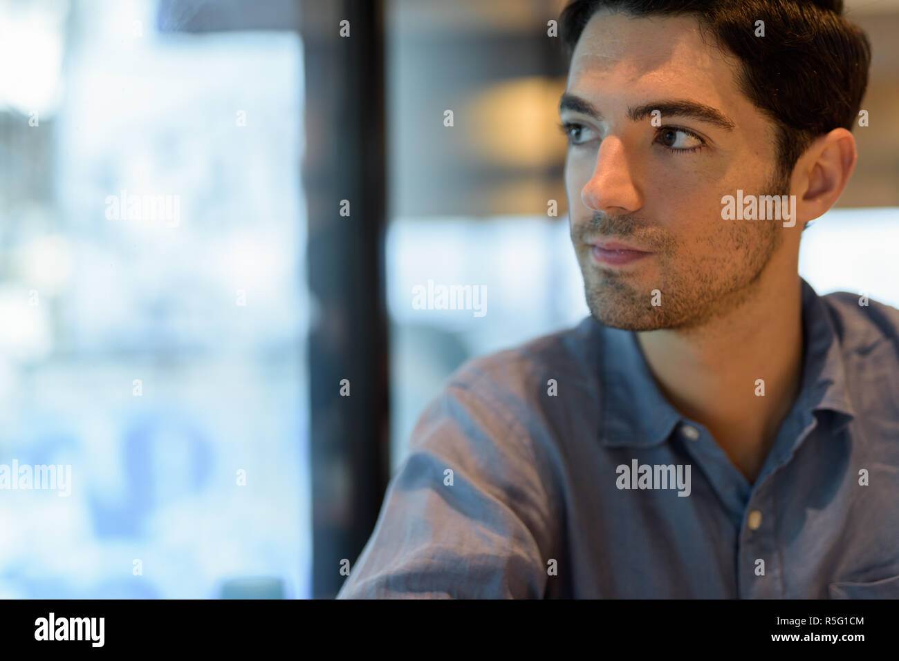 Man sitting and looking through window while thinking - Stock Image