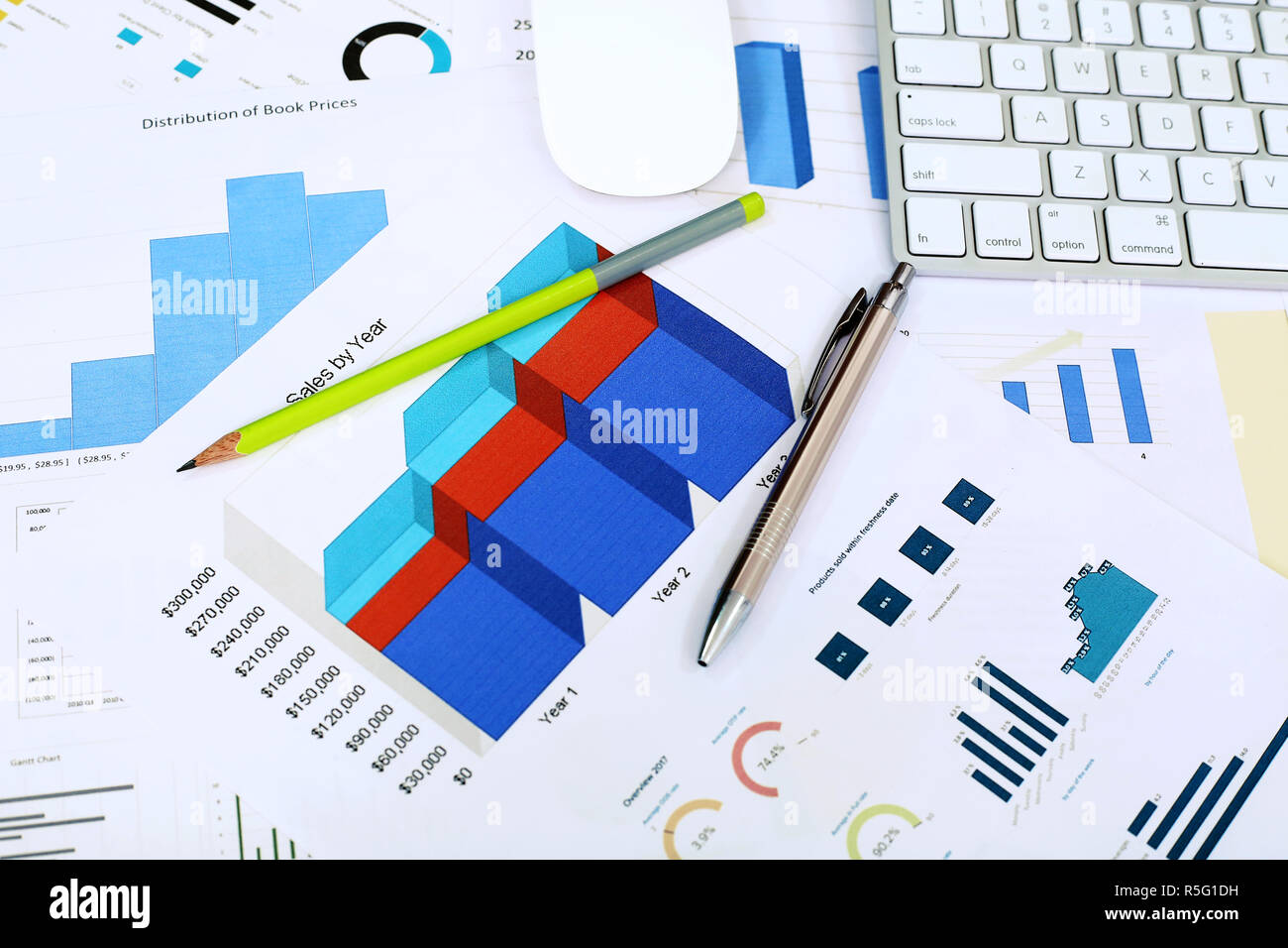 Picture of chart paper, pen, pencil, mouse and keyboard on the table. Stock Photo