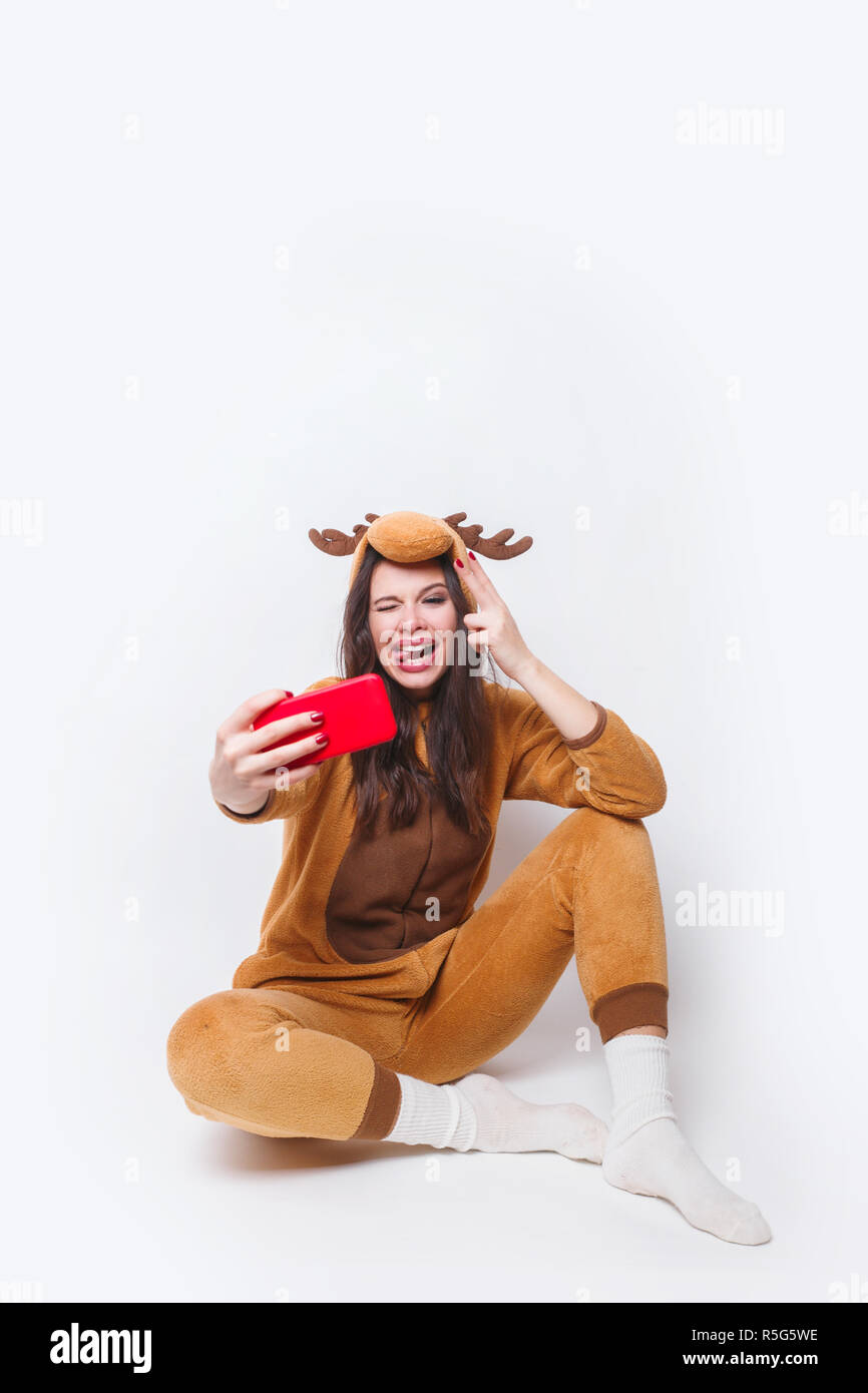 Beautifil smiling woman in pajamas deer sitting and taking selfie photo on a smartphone on a white background - Stock Image