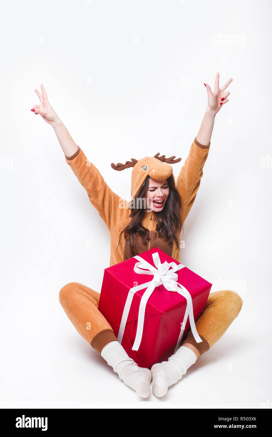 Kigurumi pajamas deer. Cute young woman in pajamas sitting with big red present box and having fun on white background . - Stock Image
