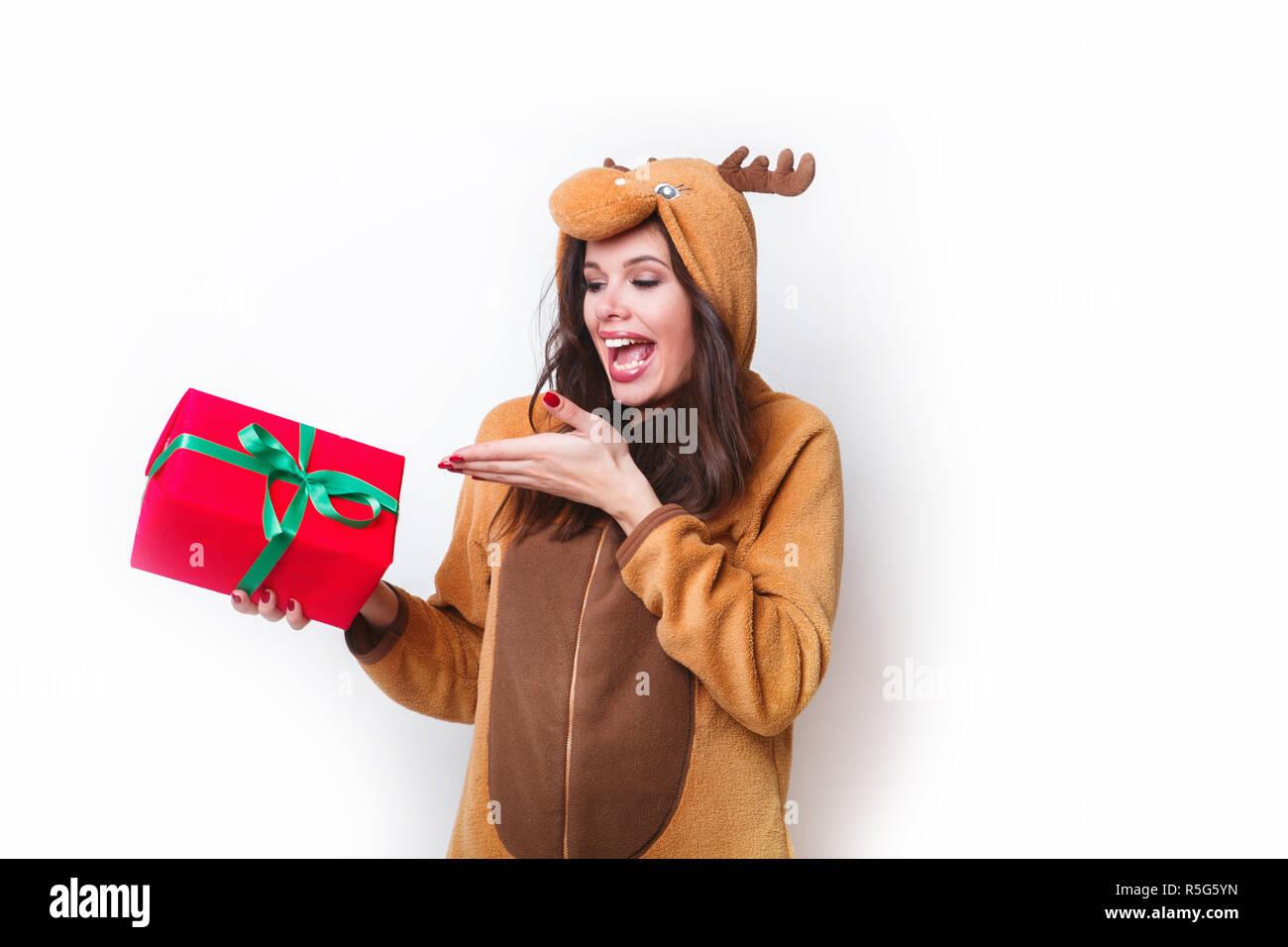 Kigurumi pajamas deer. Cute young woman in pajamas with christmas present box on white background . - Stock Image