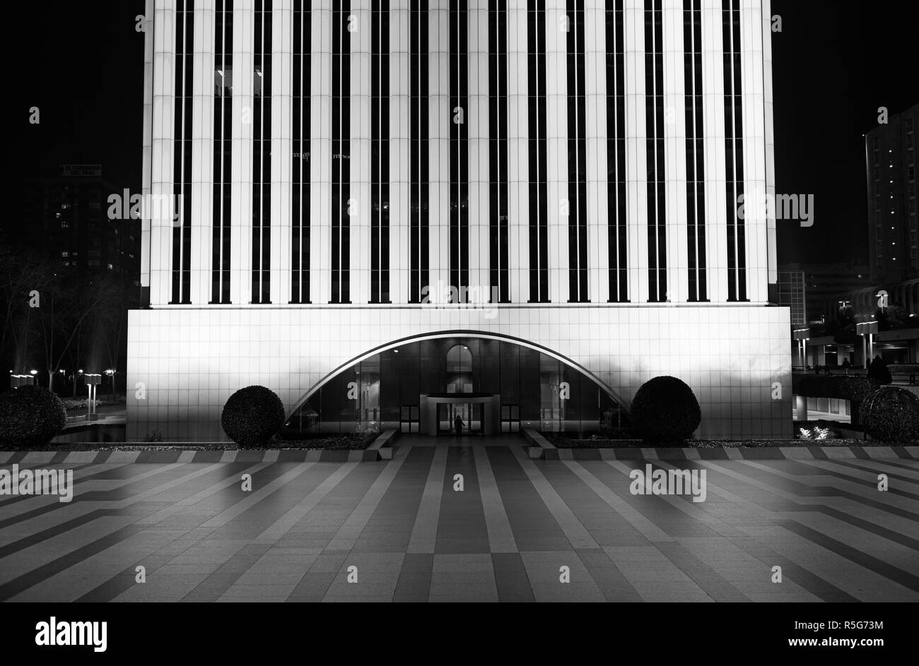 An unrecognizable person walks in the Torre Picasso building at night, in the AZCA district in Madrid, Spain. Black and white. - Stock Image