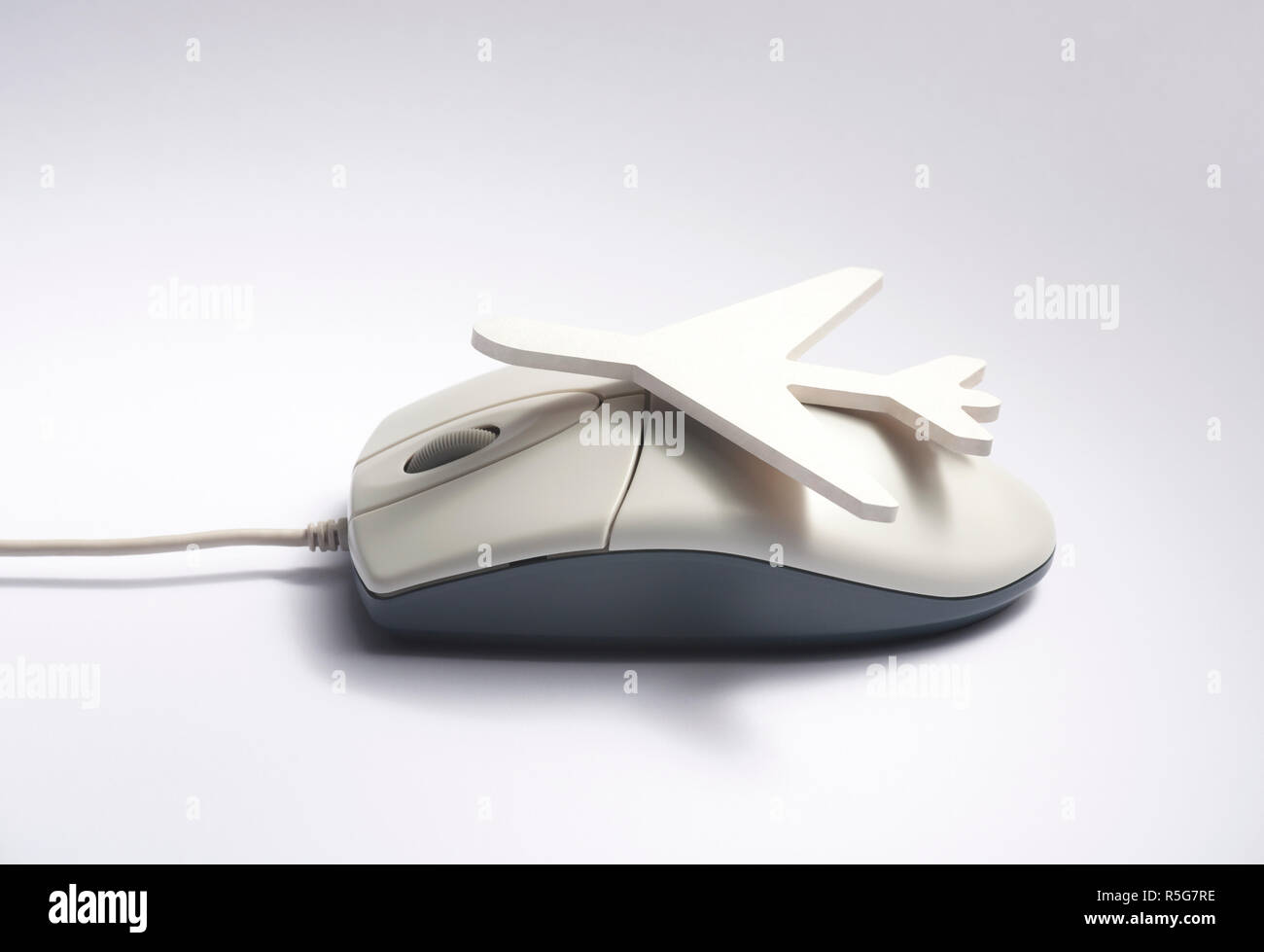 Online travel booking concept. Airplane shape on computer mouse - Stock Image