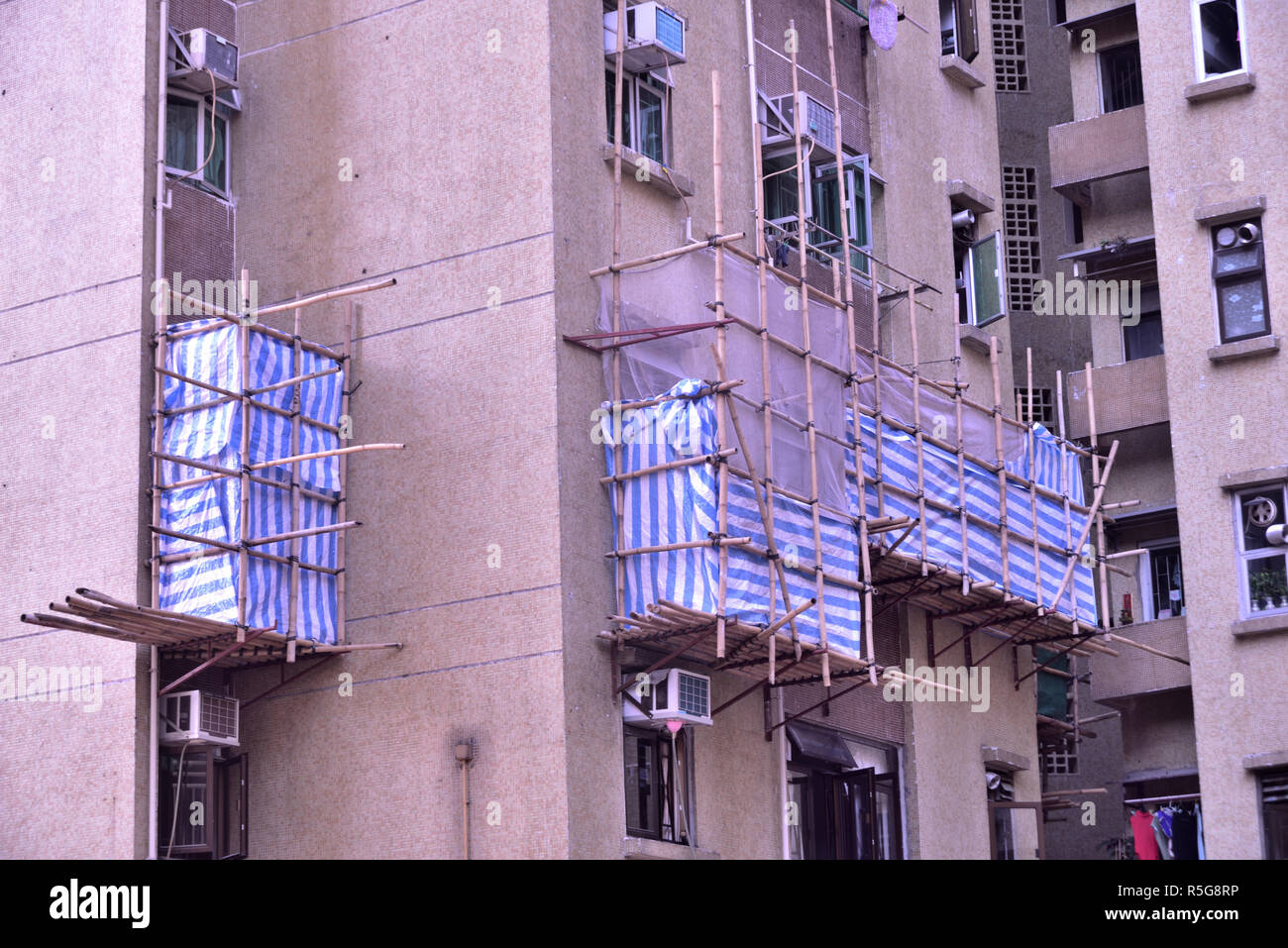 Bamboo scaffolding platforms mounted outside a building for repairing work - Stock Image