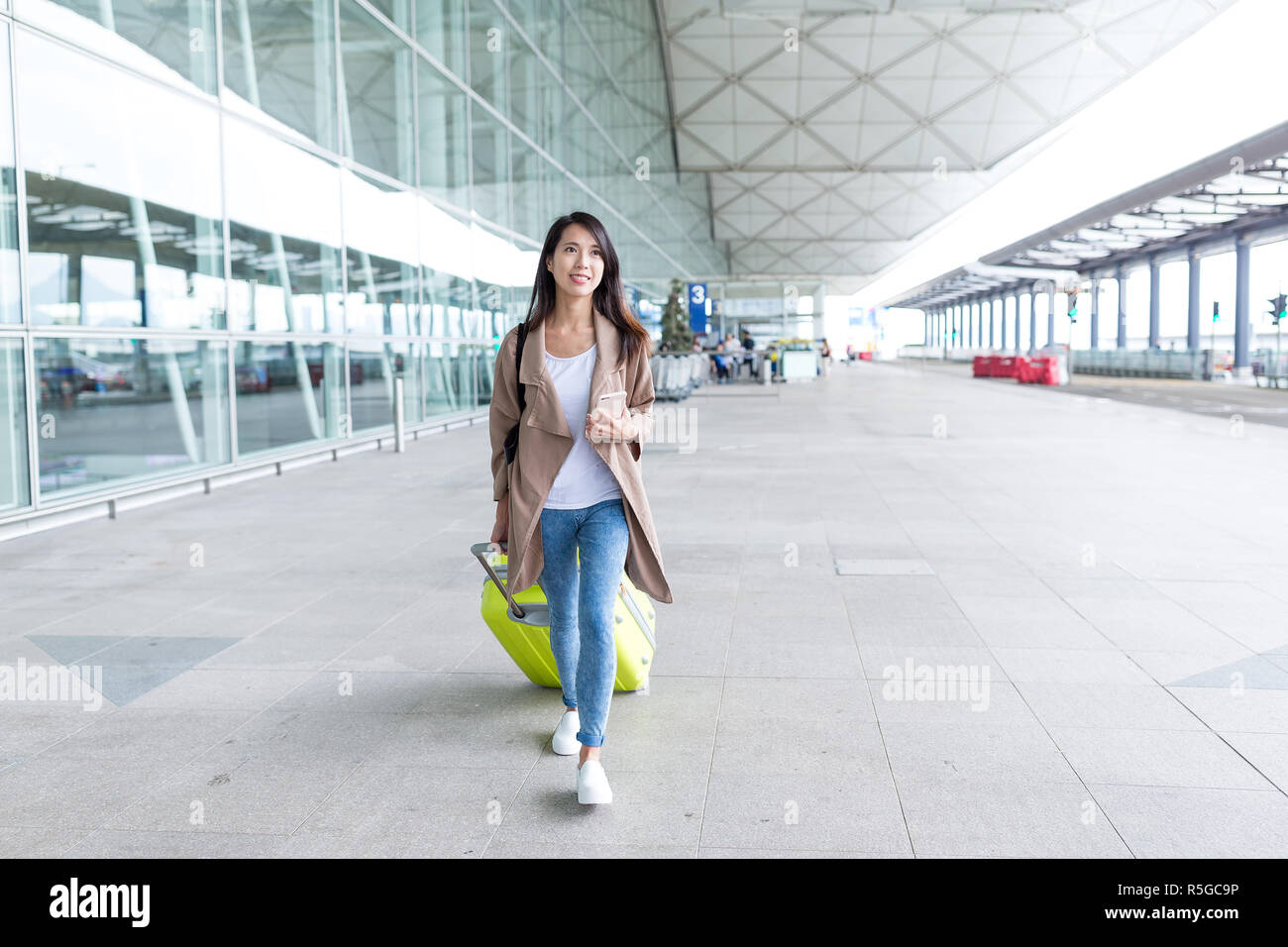 Woman walking with luggage in airport - Stock Image