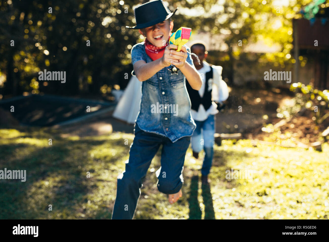 Boys outdoors having fun playing with water guns. Young boys in backyard playing with water pistols. - Stock Image