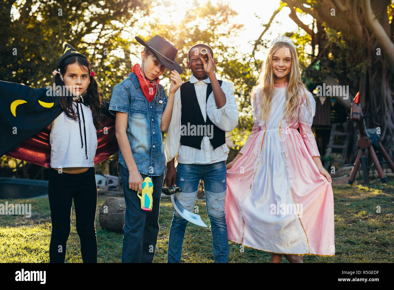 Group of kids standing in backyard garden wearing different costume. Young boys and girls having fun outdoors with superhero costumes. - Stock Image