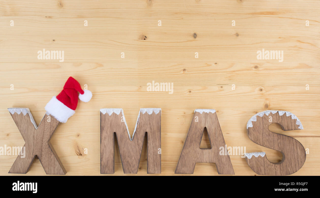 the word x mas on wood and santa hat - Stock Image