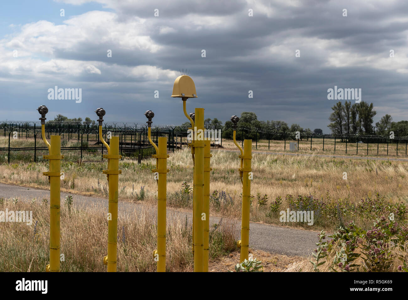 Airport Approach Lighting System at the end of a runway with heavy clouds in background. - Stock Image